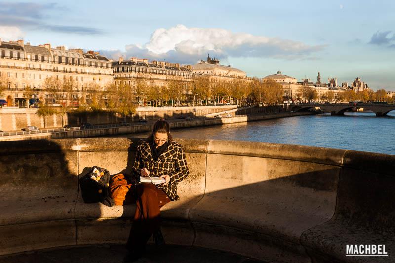 Mujer leyendo en un puente del río Sena, París, Francia