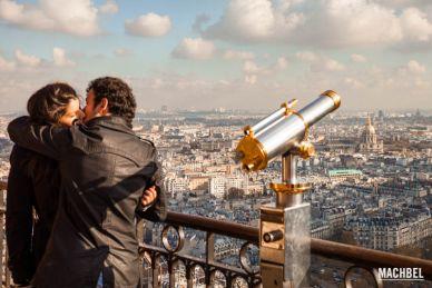 Pareja besándose al lado de un telescopio del mirador de la torre Eiffel, Paris, Francia