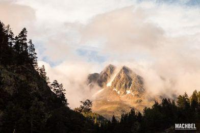 Bosque a contraluz rodea una cumbre montañosa con nieve y niebla. Ribagorza, Aragón, España