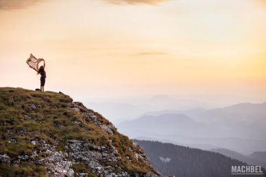 Mujer al atardecer en lo alto de una montaña